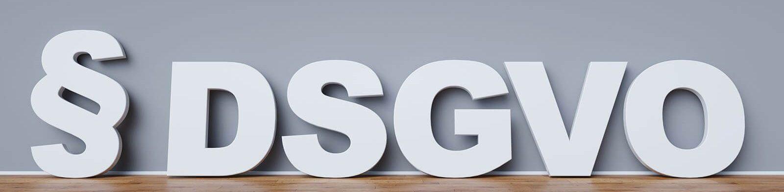 Schriftzug § DSGVO in weiß auf einem grauen Hintergrund