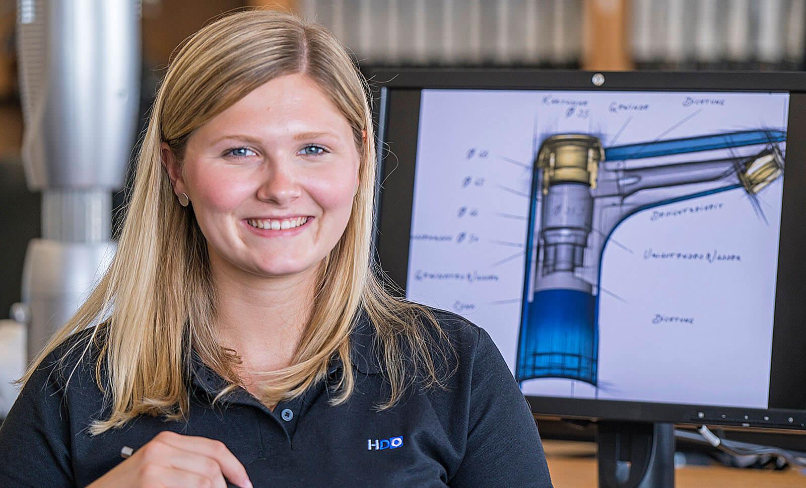 HDO Mitarbeiterin lächelt in die Kamera vor einem Bildschirm