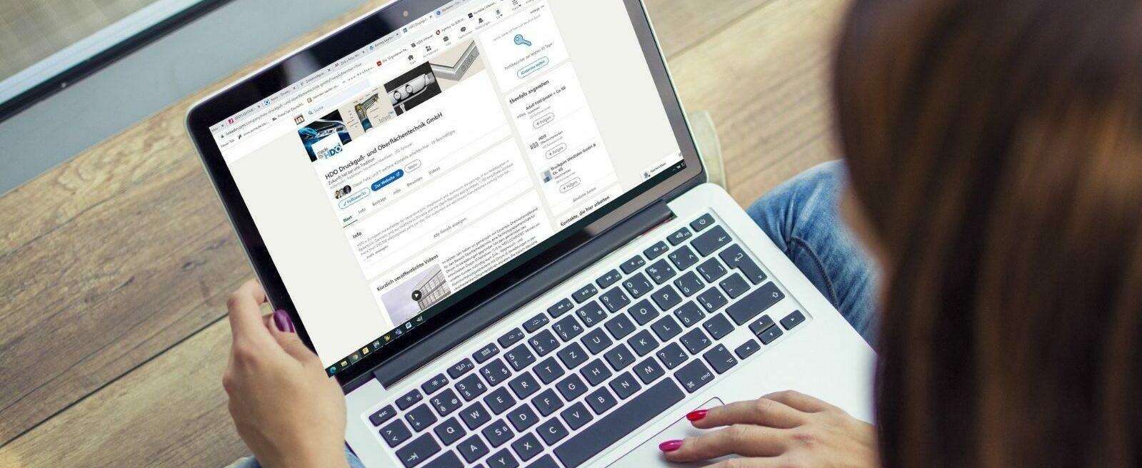 Frau sitzt am Laptop und schaut sich das HDO Linkedin Profil an